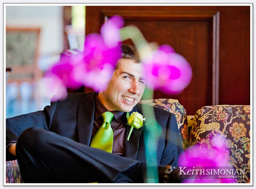 One of the groomsmen is photographed as he is framed by wedding flowers
