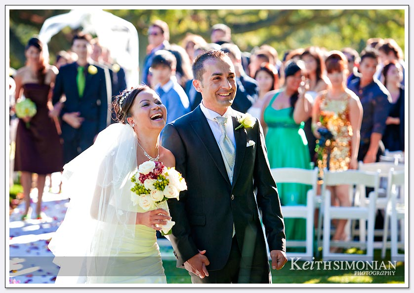 The just married couple smile and laugh as they walk down the aisle