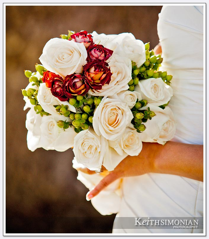 The bride holds her bouquet which has red and white flowers