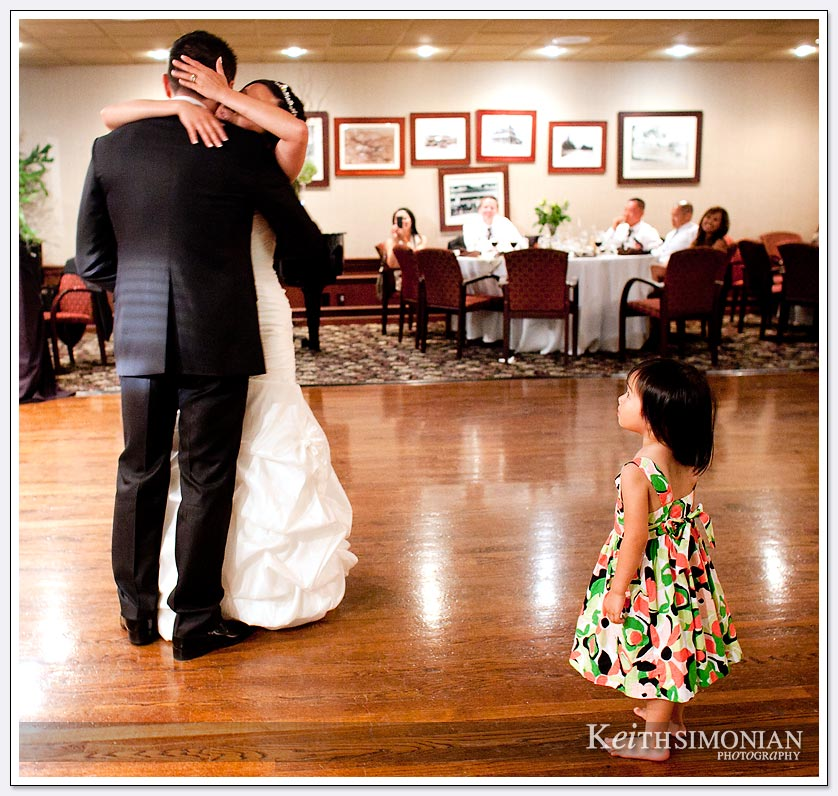 While the bride and groom enjoy their first dance a child comes closer for a better view