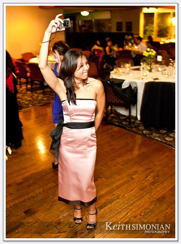 A wedding day guest is dancing and taking photos