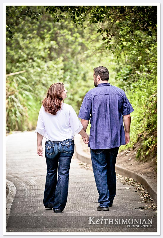 engagement photo with couple walking and holding hands