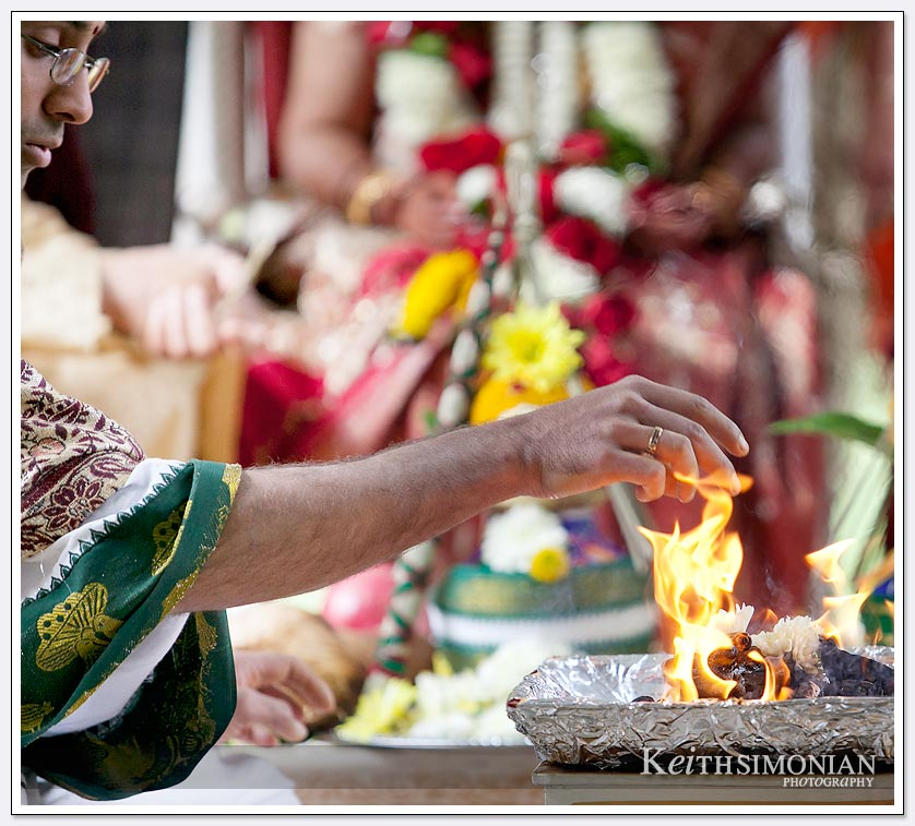 Priest appears to be touching the small flame during South Asian wedding ceremony