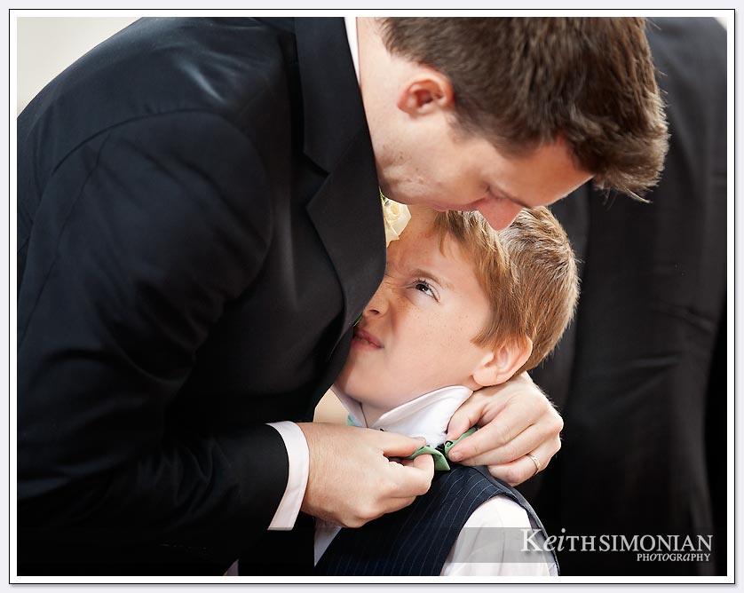 Dad puts on the finishing touches of ring bearer tie