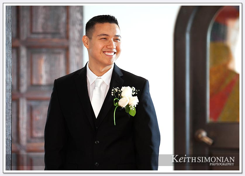 The groom is all smiles as he greats guests at his wedding ceremony