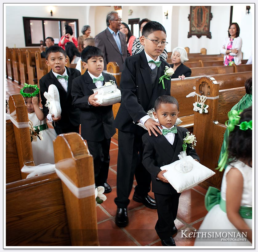 The ring bearer and helpers along with flower girls cause a traffic jam walking up the aisle