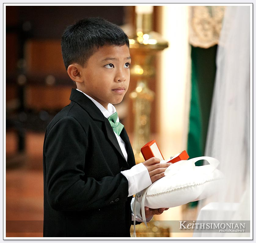 Ring bearer wearing tux waiting to hand over the rings