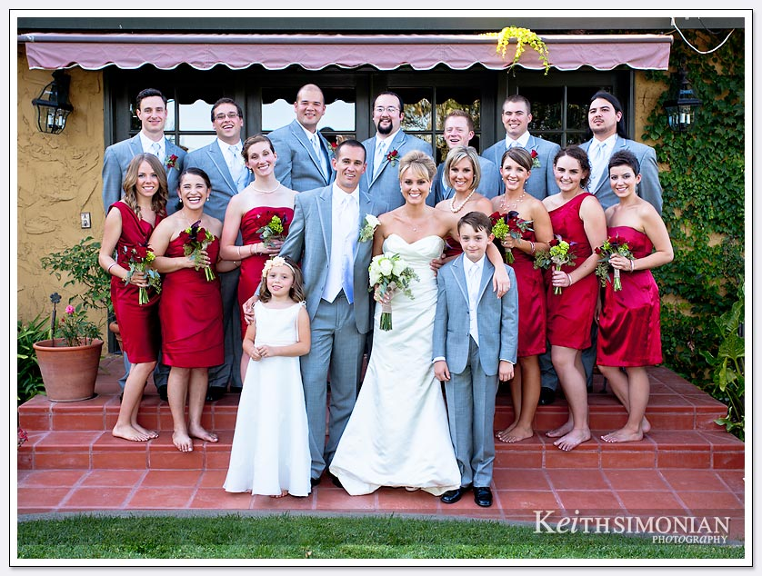 Bridesmaids wearing red dresses and groomsmen in gray tuxedos for the formal bridal party photo