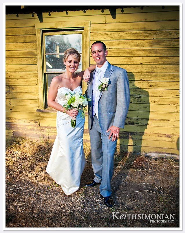 The setting sun shown on the bride and groom in front of the rustic wood building