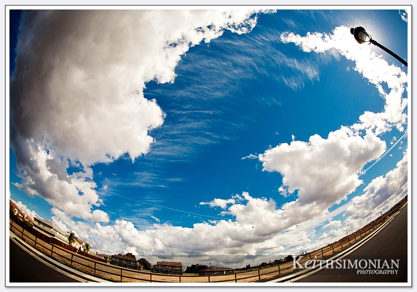 This sunny day with clouds is captured with a fisheye lens that gives the world a curved view