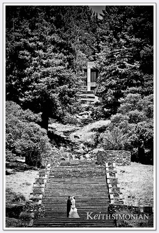 The bride and groom pose near the bottom of the 242 step granite staircase at Joaquin Miller park in Oakland, CA