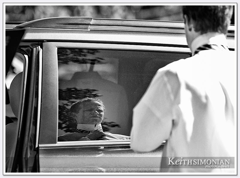 This groomsmen is using his reflection in a car window as mirror to help him tie his tie.