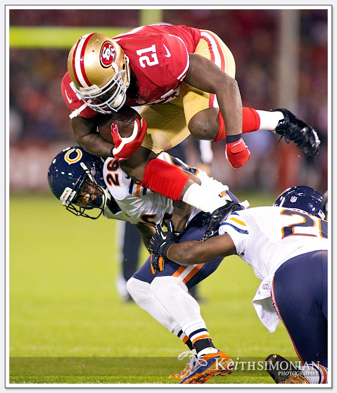 Frank Gore appears to leap over #21 Major Wright of the Chicago Bears in a Monday Night Football match up