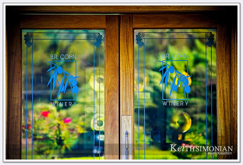 Flowers cast a reflection in the glass door of the B. R. Cohn winery in the Napa Valley