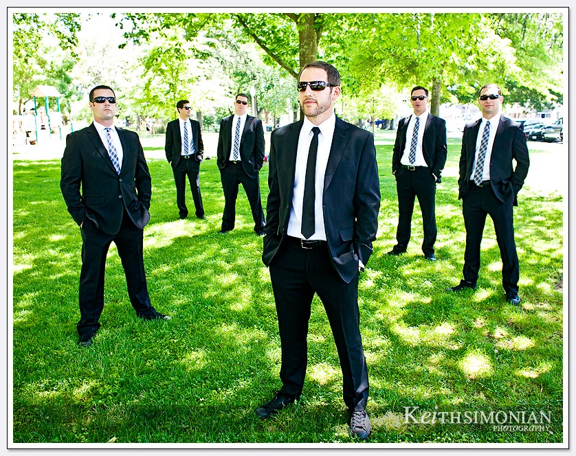 The groom and groomsmen pose for photo in park setting in the city of Sonoma.