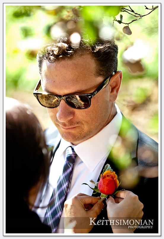 The greenery of a Napa Valley vineyard frame this photo of groomsman getting flower pinned on