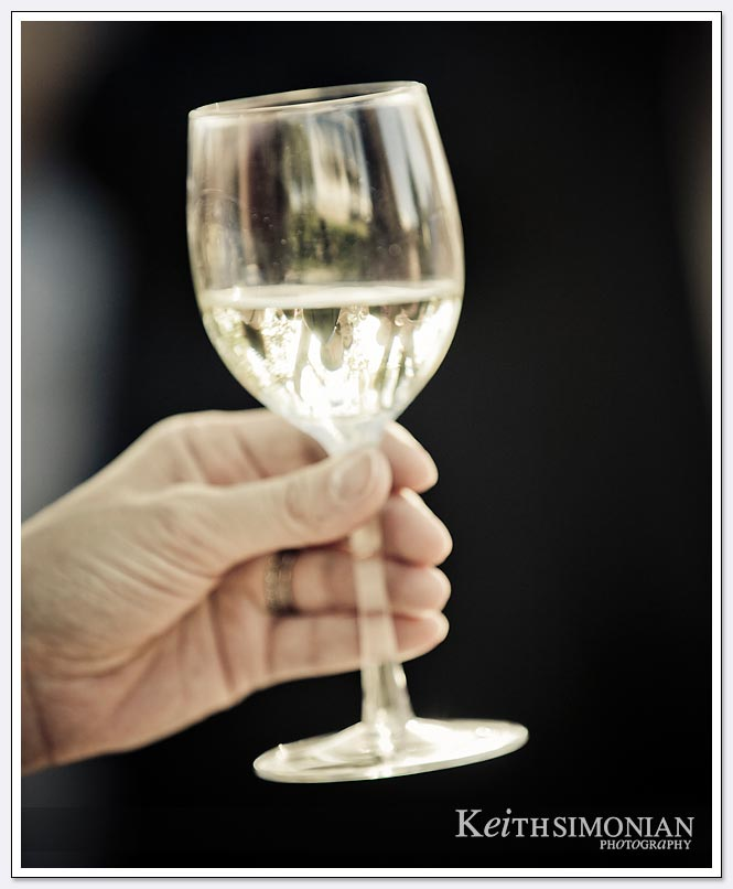 A glass of white wine that shows the reflections of other guests during the wedding reception at the BR Cohn winery