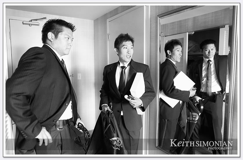 Black and white photo showing the reflections of groomsmen