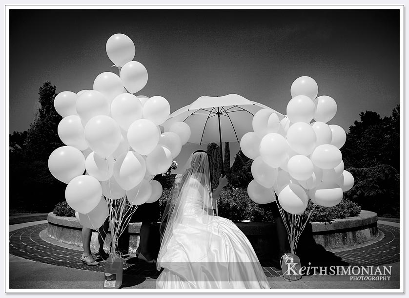 The bride waits under the umbrella surrounded by the white balloons the will be released at the end of wedding ceremony