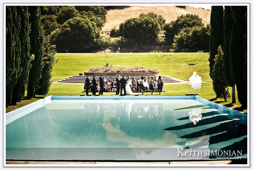 The wedding ceremony as seen across the reflection pool at Pulgas Water temple