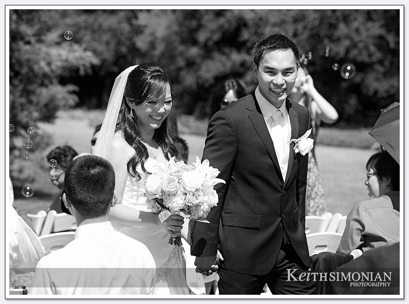 The just married bride and groom walk down the aisle in this black and white photo