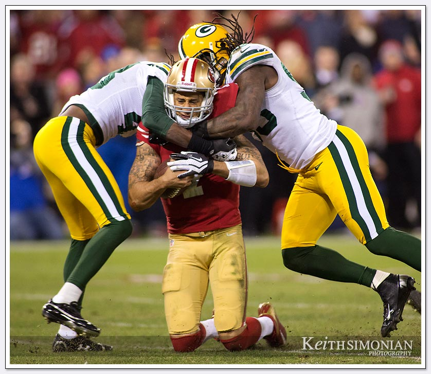 49ers quarterback Colin Kaepernick is double teamed by Green Bay Packer defenders