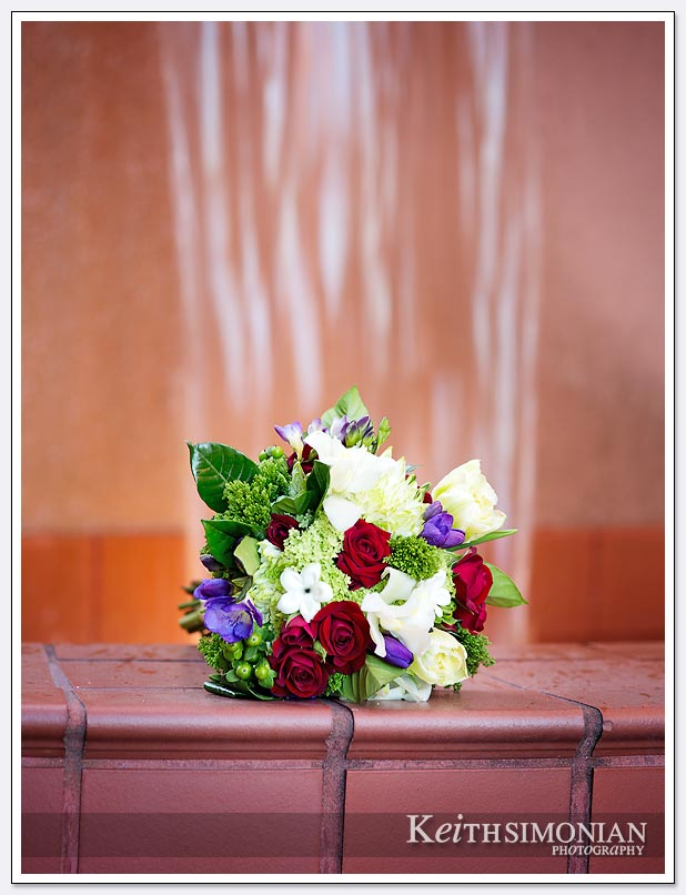 The bride's bouquet sits in front of the water fall by the red brick