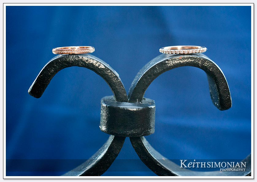 The brides wedding rings sits atop the gate with wonderful blue background
