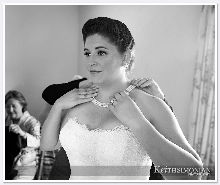 The bride puts on her pearl necklace before her wedding at the Clos La Chance winery in San Martin