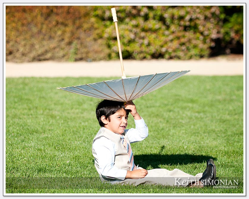 Child playing with umbrella before wedding ceremony