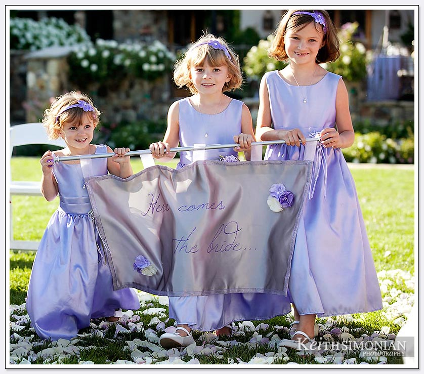 Three girls carry sign that says here comes the bride