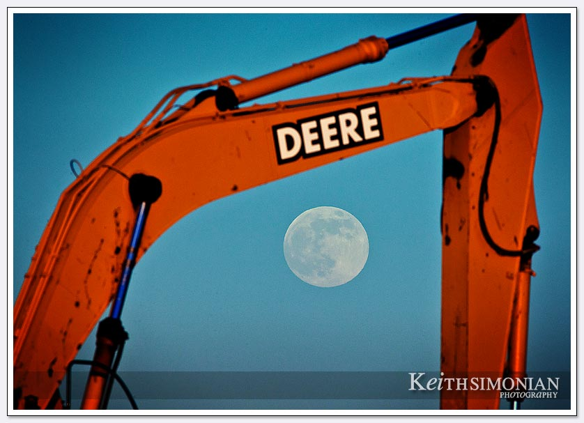 The 2013 supermoon rises in the early evening sky behind a John Deere 270lc crawler excavator