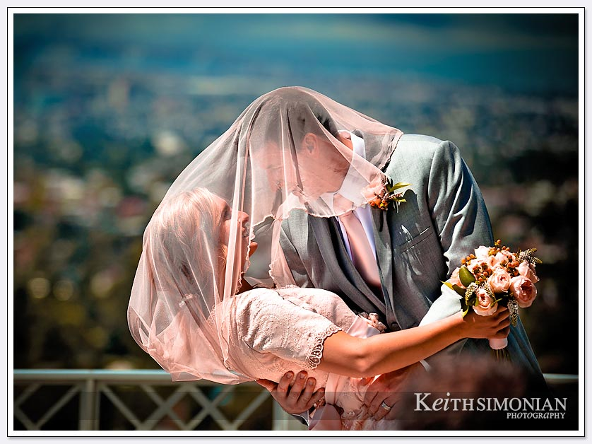 The bride and groom embrace under the veil with San Francisco in the background