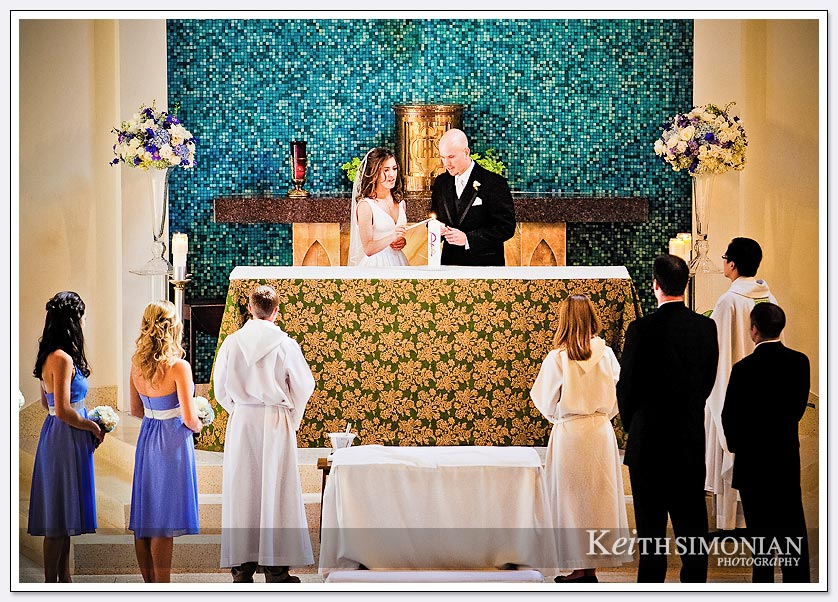 The bride and groom light the unity candle during a wedding at Our Lady Queen of Angels in Newport Beach
