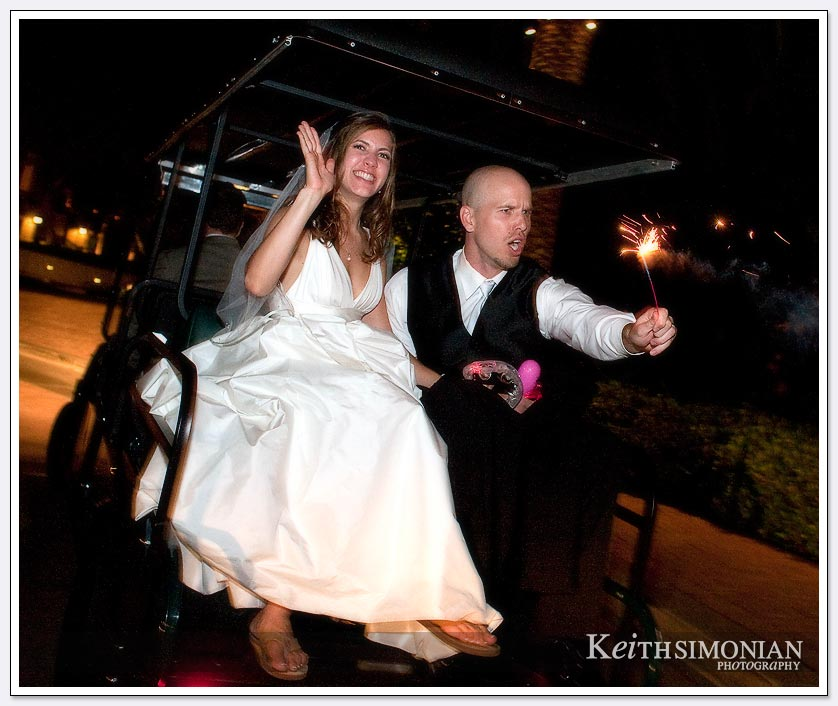 The bride and groom ride off in a golf cart after their Platinum wedding reception at the Pelican Hill Resort in the Mar Vista Ballroom