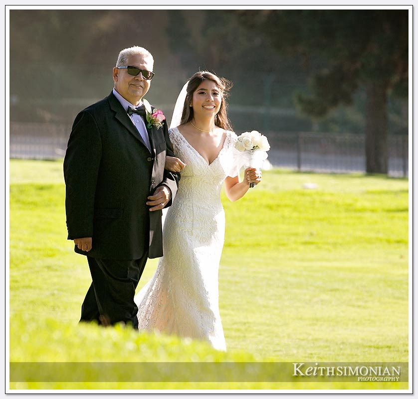 The bride and her father walk from the golf course to the ceremony at The Lakes at El Segundo Wedding