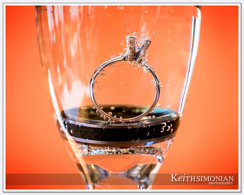 The bride and grooms wedding rings as are placed in a champagne glass