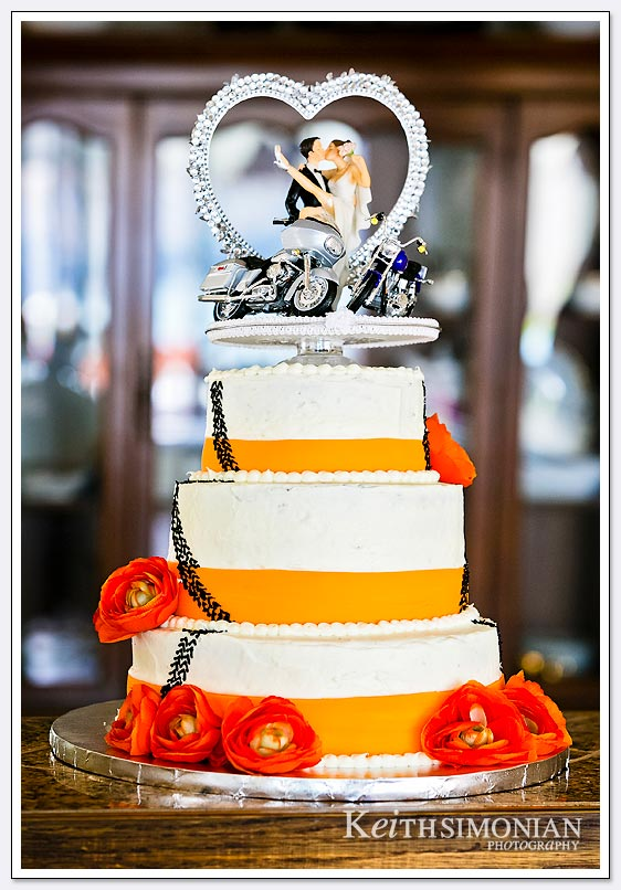 The orange and white wedding cake featured motorcycles as both the bride and groom ride.