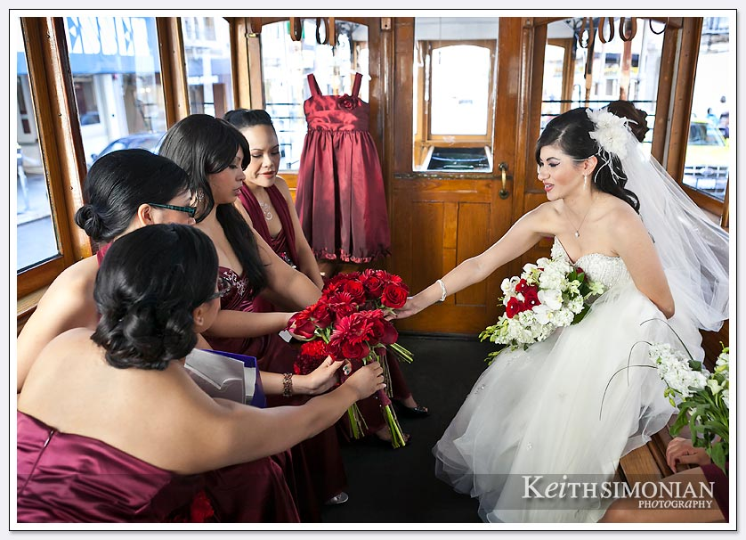 Bride with bridesmaids in red dresses ride trolley to St. Ignatius church in San Francisco.