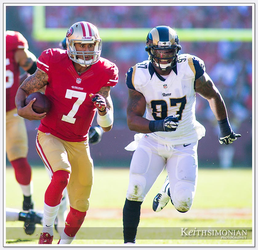 During their December 1, 2013 matchup San Francisco quarterback #7 Colin Kaepernick runs away from St. Louis Ram defensive end #97 Eugene Sims