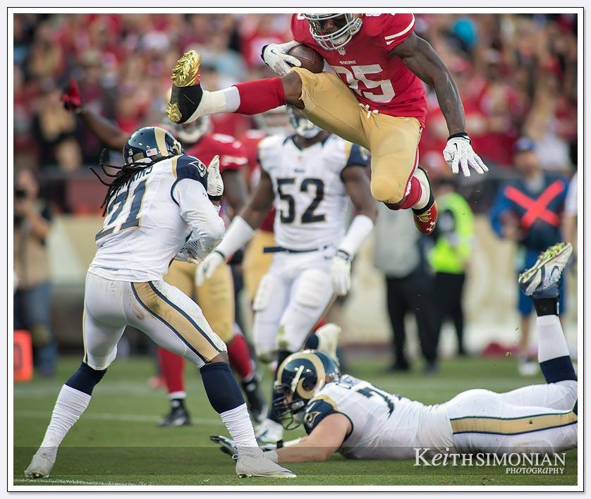 #85 San Francisco 49er Vernon Daivs leaps over St. Louis Ram  #21 Janoris Jenkins to score a touchdown