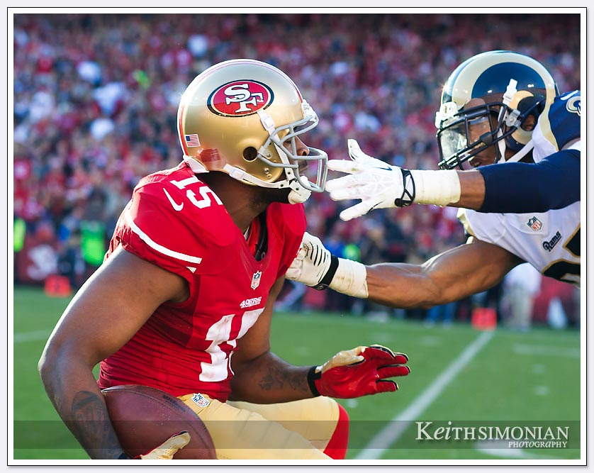 San Francisco 49er #15 Michael Crabtree ducks away from a St. Louis Ram defender on a 60 yard pass reception.