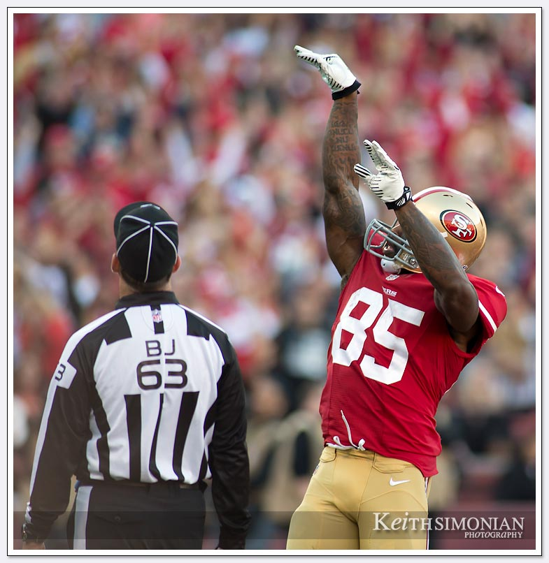 #85 San Francisco 49er Vernon Davis shoots the football through the uprights after a touchdown as back judge Jim Quirk watchers.