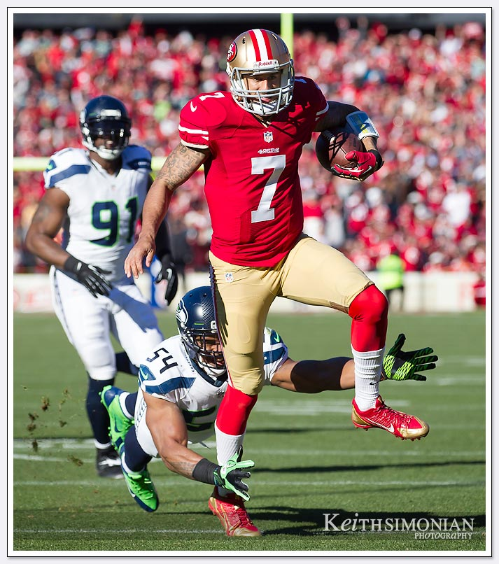 SAN FRANCISCO, CA - DECEMBER 08: Colin Kaepernick #7 of the San Francisco 49ers running with the ball tries to leap away from Bobby Wagner #54 of the Seattle Seahawks during the first quarter at Candlestick Park on December 8, 2013.