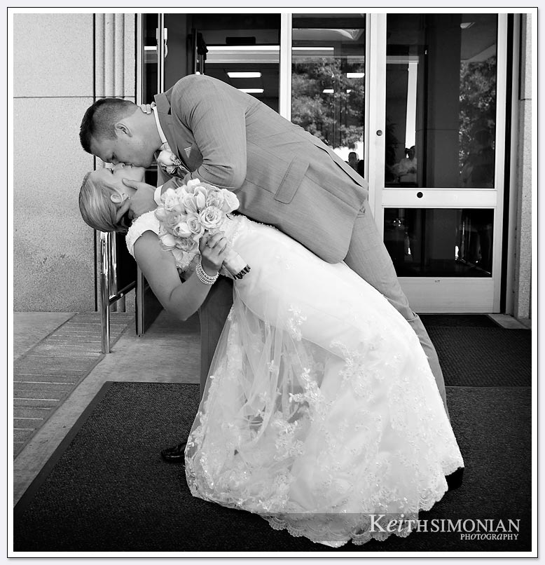 The groom dips the bride and kisses her outside the Oakland LDS temple