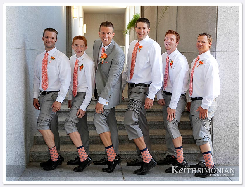 The groom and groomsmen pose for picture showing their matching socks outside Oakland LDS temple