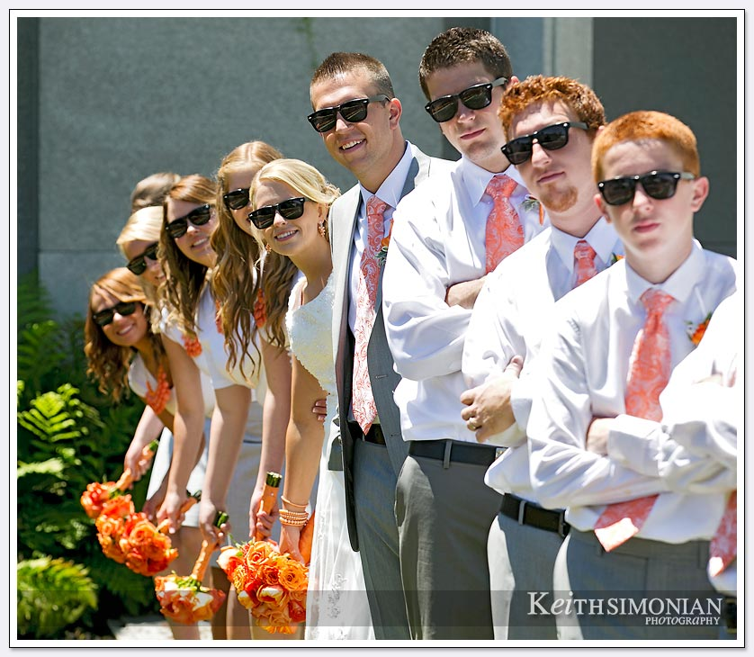 The entire wedding party poses for photo wearing sunglasses by the Oakland LDS temple