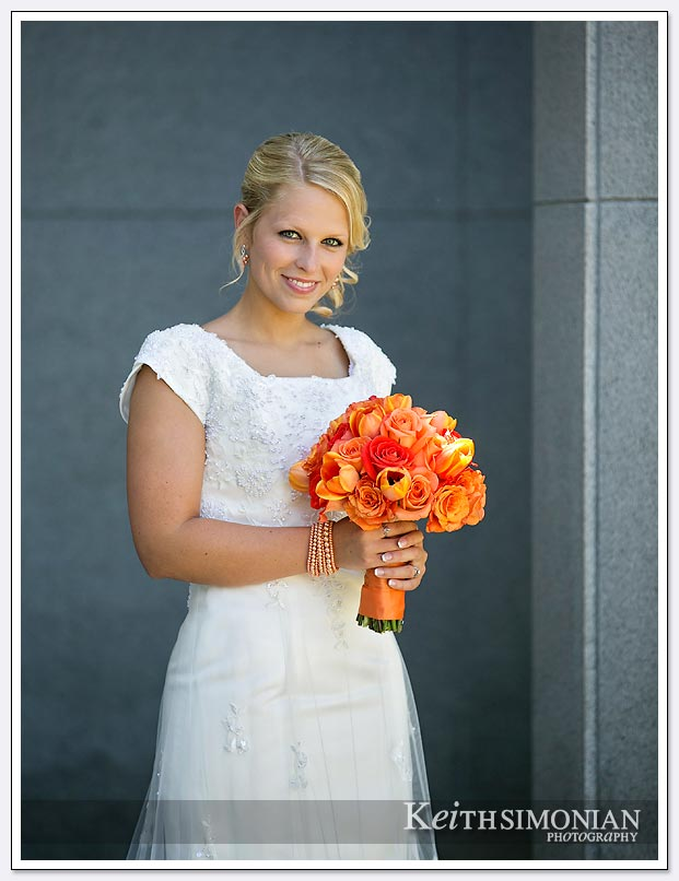 The bride poses outside the Oakland LDS temple with her bouquet