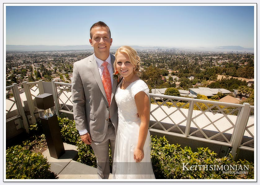 The bride and groom pose with the San Francisco Bay area in the background outside the Oakland LDS temple