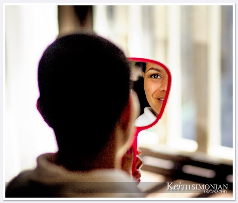 Bride views herself in mirror while getting ready in Le Meridien Hotel in San Francisco